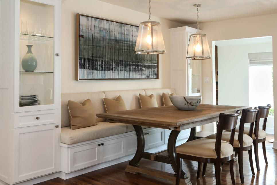 built in kitchen table antiqued cabinets a banquette is flanked by tall glass for storing dishes and glassware while trio of chairs provides more seating on the other side