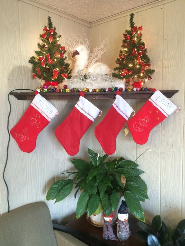 Mini Christmas trees with a handmade swan with stockings hanging below. We can't forget the handmade snowmen on the table made from mason jars and scrap fabric/material.