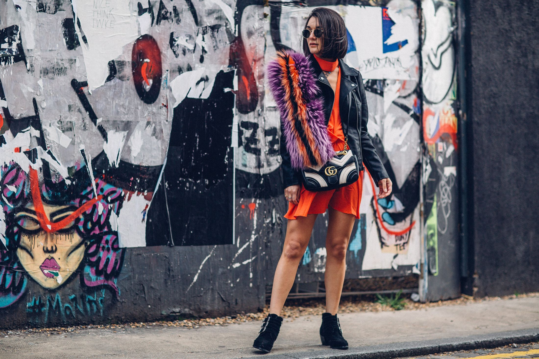 Anisa Sojka styles Brand Attic orange choker dress | Black Only faux leather biker jacket | Western silver buckle ankle boots | Round classic Rayban sunglasses | Striped Gucci CC marmont cross-body bag with gold chain | Purple fur stole over the shoulder | Brunette straight shoulder length hair | Fashion blogger street style shot by Moeez Ali in the graffiti streets of Shoreditch, London