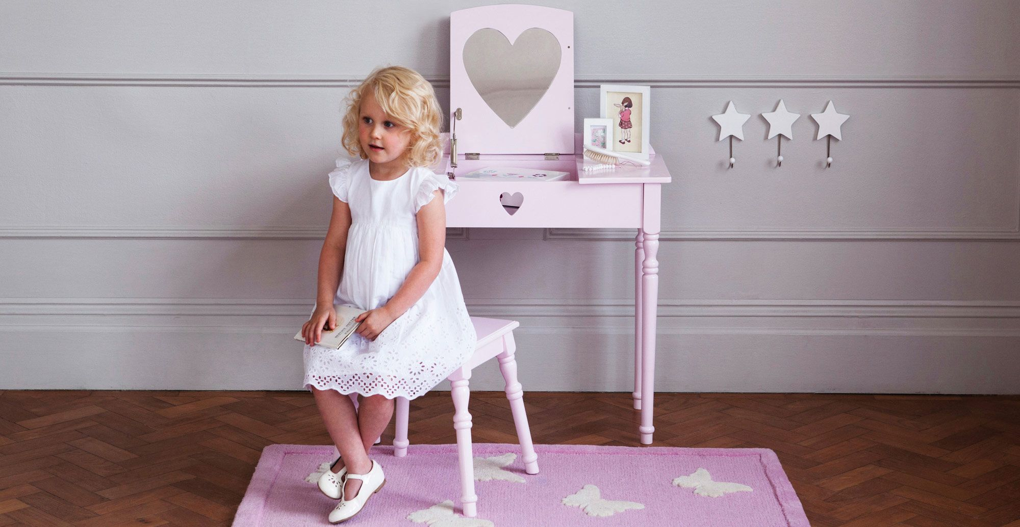 A pretty pink dressing table and stool set for little girls; it's great for storing hair accessories and trinkets.