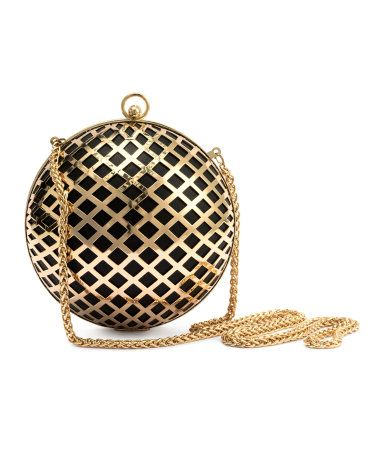 Round clutch bag in perforated-patterned metal and imitation leather. Metal  chain shoulder strap and fastener at top. One large inner compartment. 3ae2eabeb9a1