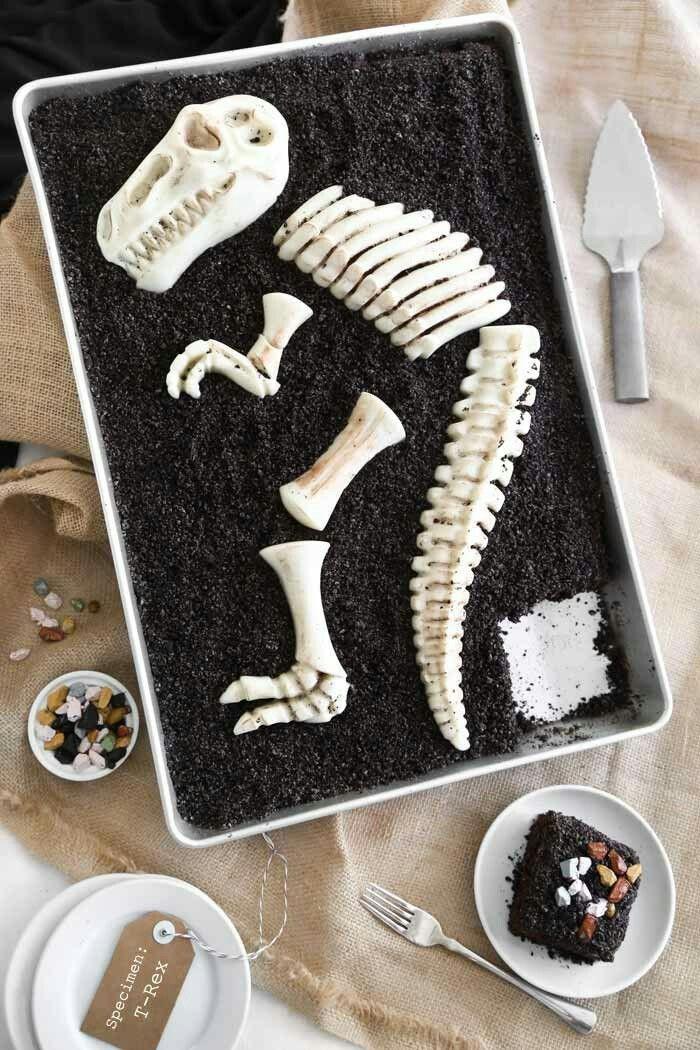 Fossiltårta   Den här tårtan ser så mycket svårare ut än den är, egentligen är det bara en chokladkaka som fått ett glasyr och pulvriserade Oreo-kakor över sig.Det bygger lite på att du kan få tag på en form för själva skelettet, men de ska finnas som sandformar för sandlådan!