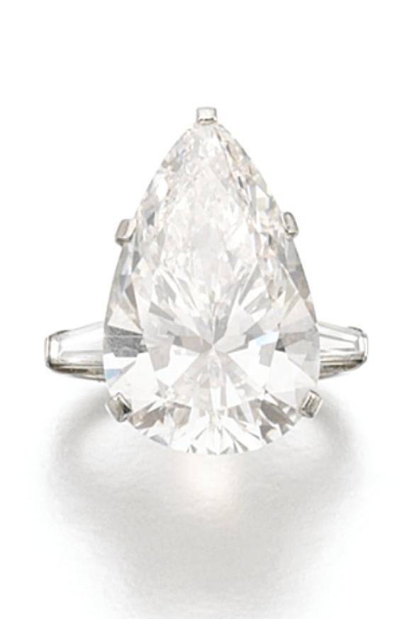 DIAMOND RING, BULGARI, 1975 The pear-shaped diamond weighing 14.44 carats, between tapered baguette diamond shoulders, size 51, signed Bulgari. diamond