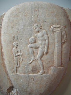 Ancient Greek football player balancing the ball. Marble grave stele of the 4th century BC found in Piraeus