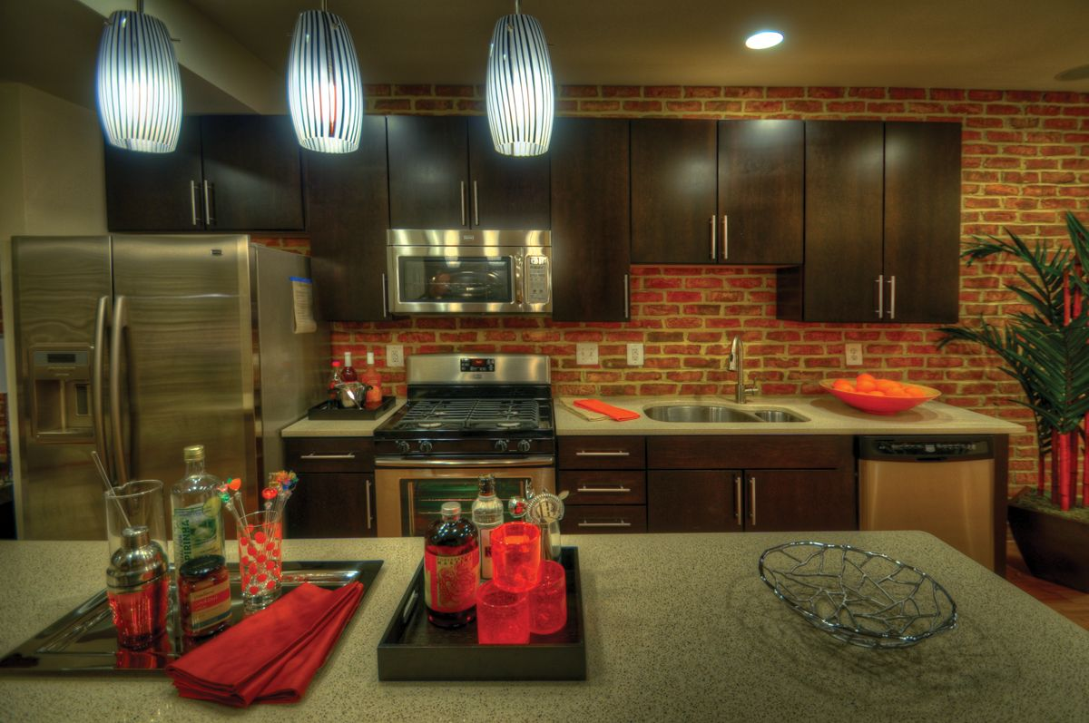 Entertainer S Kitchen In A Townhome Model In Frederick Md Exposed Brick Pendant Lights Black Cabinets Stai Entertaining Kitchen Outdoor Appliances Kitchen
