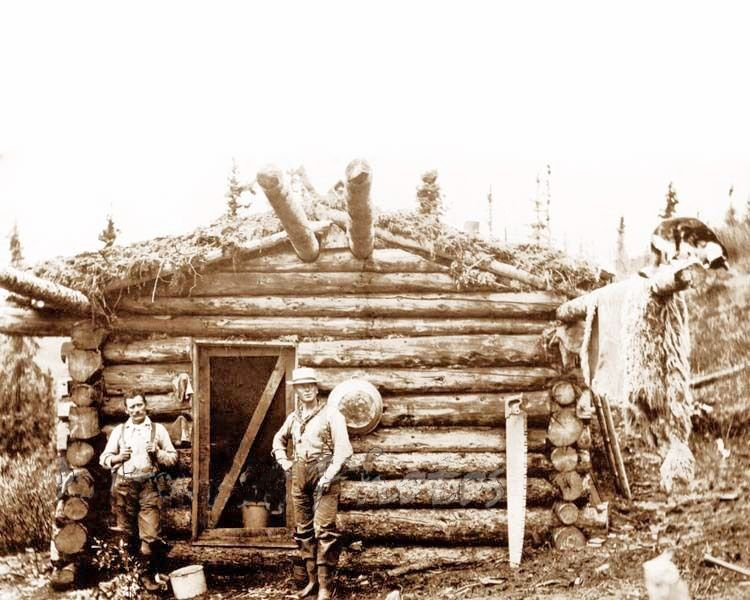 EARLY 1900'S HUNTERS AT A LOG CABIN & HANGING HIDE SKIN.