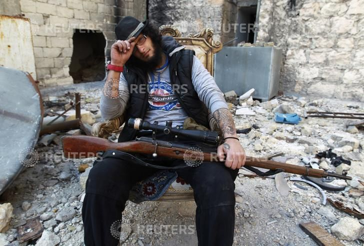 Khattab al-Halabi, a former tattoo artist who is now a Free Syrian Army fighter, poses with his weapon at the Karm al-Jabal frontline in Aleppo February 23, 2014. Picture taken February 23, 2014. REUTERS/Jalal Al-Mamo (SYRIA - Tags: POLITICS CIVIL UNREST CONFLICT SOCIETY)  http://picturesstatic2.reuters.com/Doc/RTR/Media/TR3/0/a/0/4/RTR3FPAU.jpg