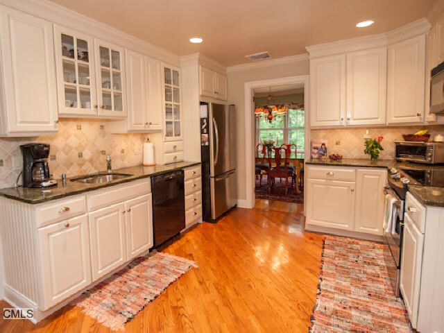 View of Kitchen with white cabinets and hardwood floors in ...