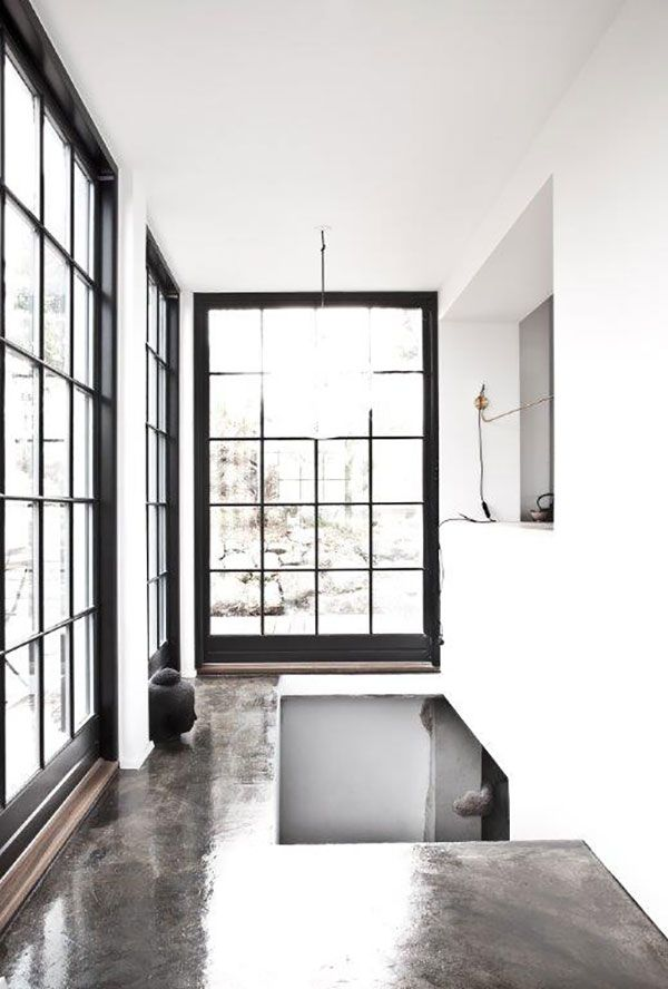 Brown polished concrete floor, white walls, doors/windows with black ...
