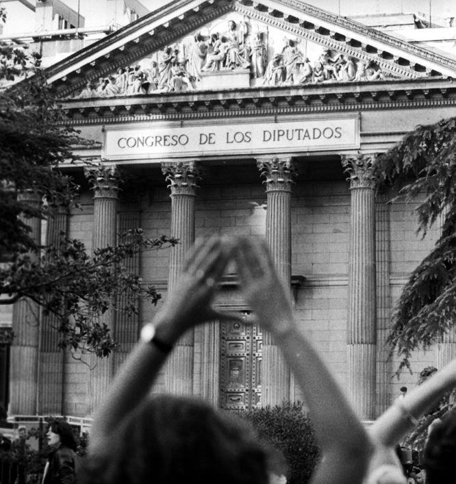 4 de octubre de 1983 Una mujer hace el signo feminista en una manifestación a favor del aborto libre y gratuito a las puertas del Congreso de los Diputados, durante el debate sobre la despenalización parcial del aborto en casos de violación, grave peligro para la vida de la madre y malformaciones. MARISA FLÓREZ