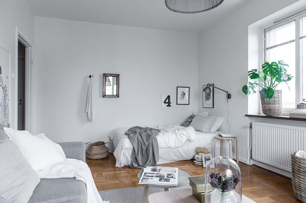 Minimalist and monochromatic studio apartment with art photos on the ...