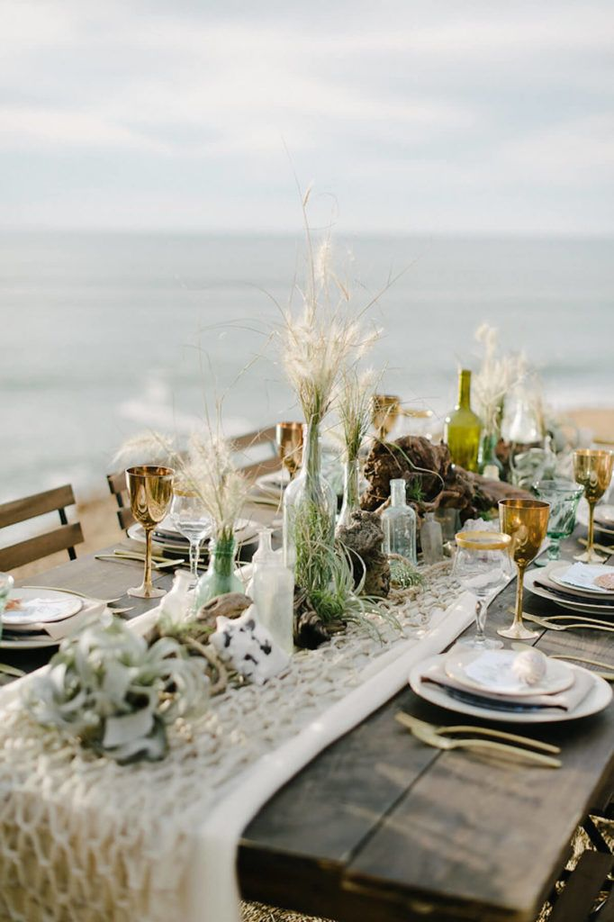 Decorative Fish Netting Over Neutral Table Runner And Beachy Bottles Beach Wedding Tables Beach Table Decorations Beach Table