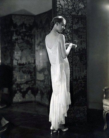 Marion Morehouse, in the apartment of Conde Nast, wearing a beaded white chiffon dress by Chanel, and ankle-strap shoes by Delman, photo by Edward Steichen, 1927