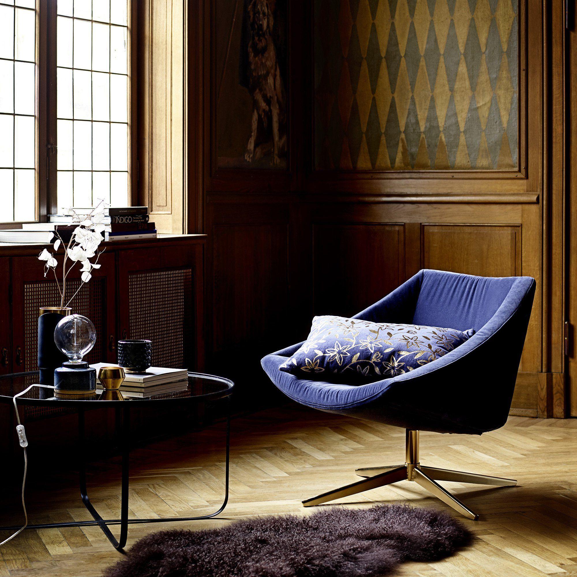 Un fauteuil en velours bleu avec pied en laiton doré dans un salon