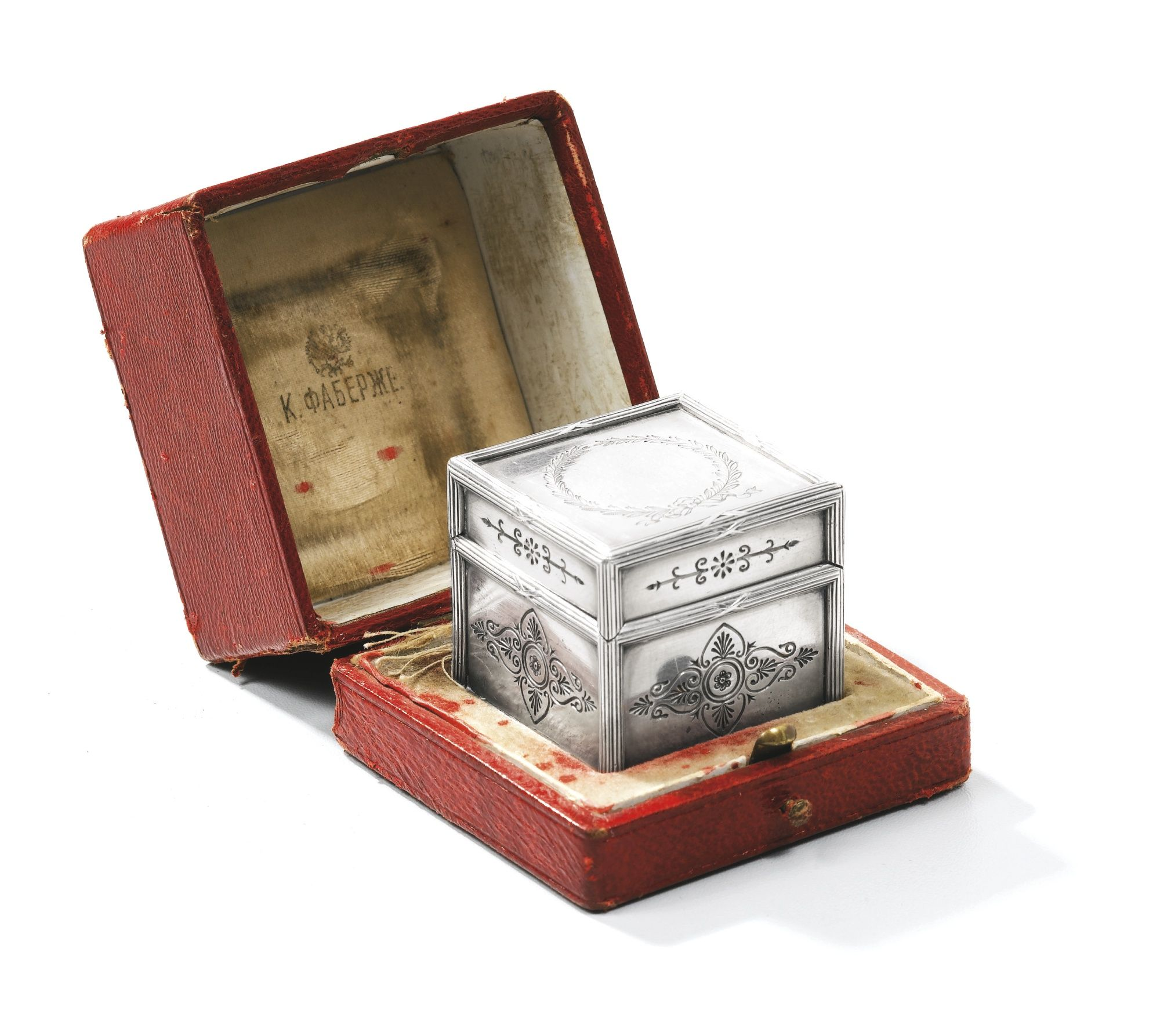 A Fabergé silver travelling inkwell, workmaster Theodore Ringe, St Petersburg, circa 1895, the sides engraved with fleurons, the lid with a wreath, raised bound reed borders.