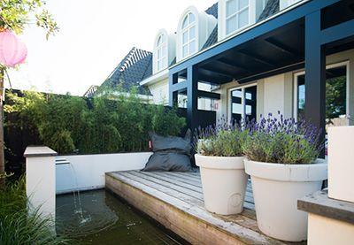 Eigentijdse tuin met waterpartij en veranda in Amersfoort