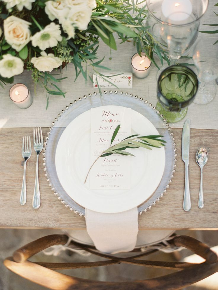 wedding reception place settings with greenery