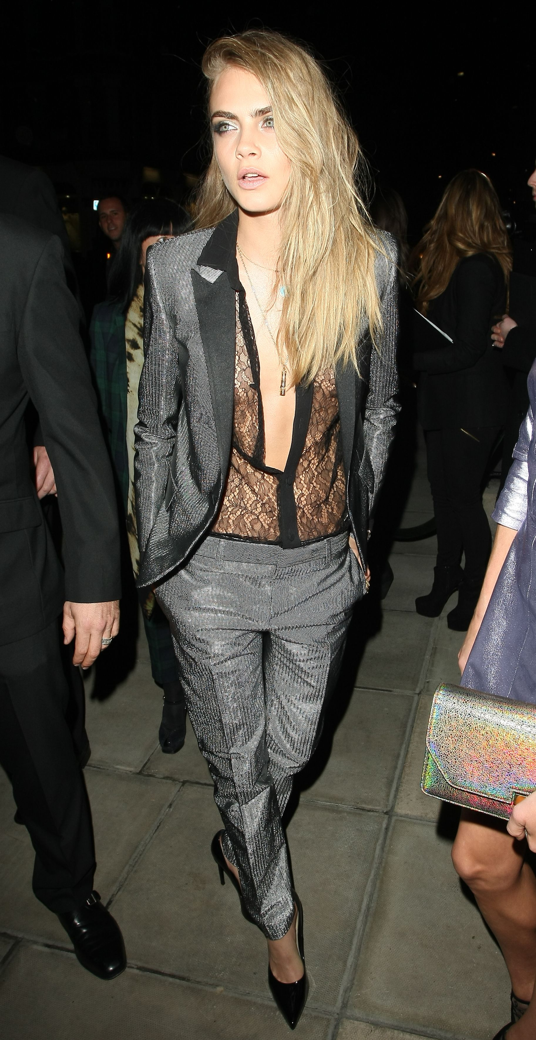 50b787f470ca Cara Delevingne stunned back in London town as she went braless in a sheer  lace blouse underneath a metallic trouser suit.