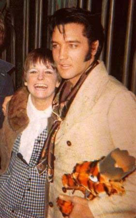 Elvis Presley talking and posing with fans outside of CA home