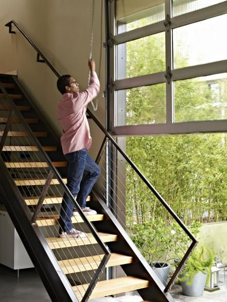 To raise the garage door, Mark simply stands on the stairs, then pulls back a rotating chain that locks in place.