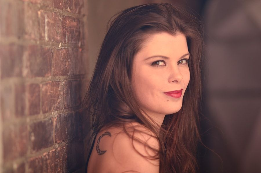 Portrait of young woman with brown hair along a red brick wall