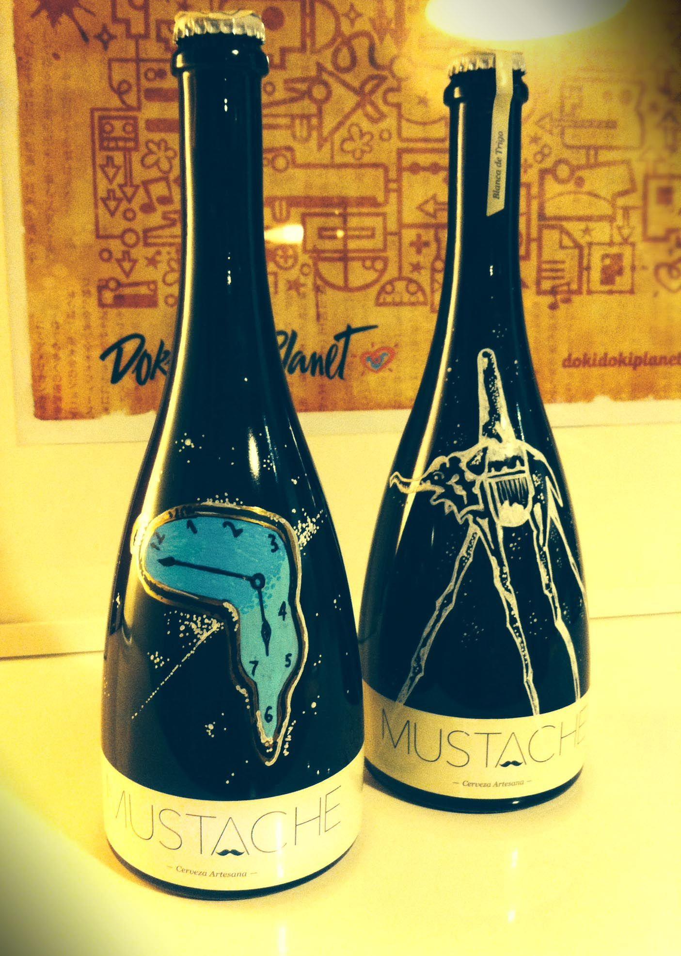 """Botellas de cerveza Mustache pintadas a mano para la exposición de Dalí en Malasaña organizada por la galería """"Despacio arte y vino"""""""