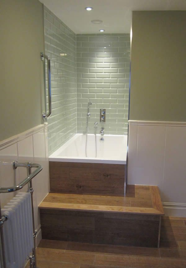 The Calyx soaking tub inset in awooden surround with built-in step ...