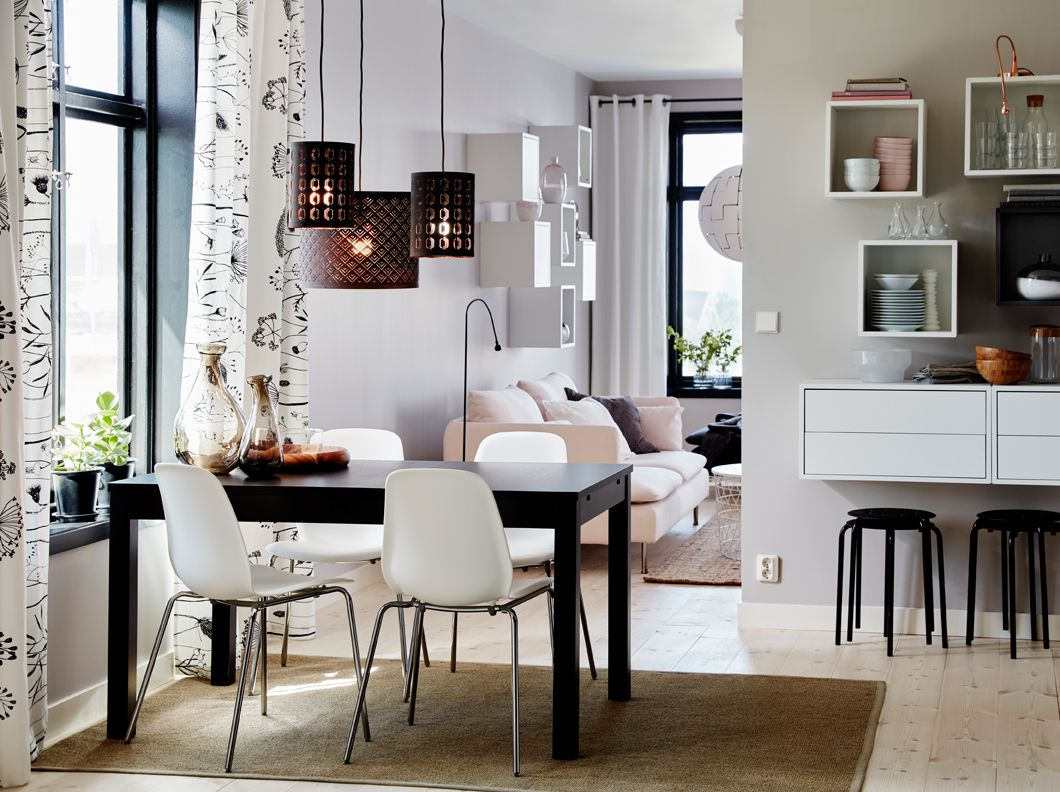 a medium sized dining room furnished with a brown black table with room for six people and four white chairs with scooped seat and chrome plated legs - Ikea Dining Room Ideas