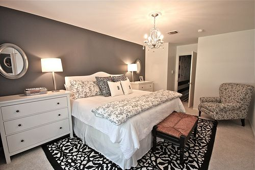 This wall colour then luxurious striped wallpaper feature wall behind four poster bed