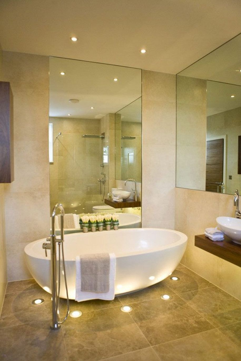 Bathroom beautiful white free standing bathtub and large wall mirror on contemporary bathroom design also brown floor tile cool water for sweet moment in