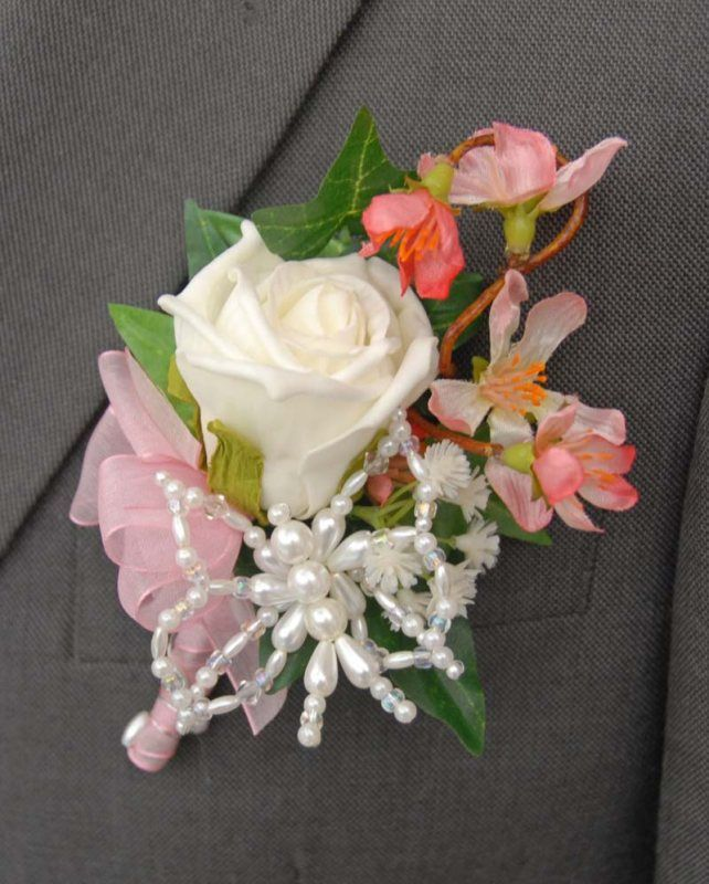 Grooms handmade buttonhole with an ivory rose,  a loop of ivy, two small sprays of cherry blossom, ivory gypsophila,  and a light pink organza bow with a matching handle.  With a beautiful and delicate handmade beaded butterfly with a selection  of beads and pearls.
