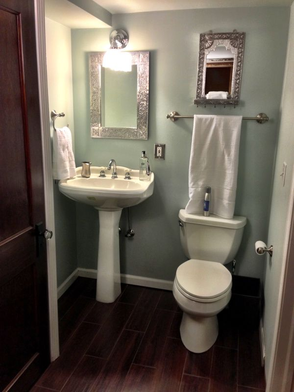 Just toilet and pedestal sink  wood tile floors  sleek and simple     Just toilet and pedestal sink  wood tile floors  sleek and simple with  smart finishes  Excellent half bath space