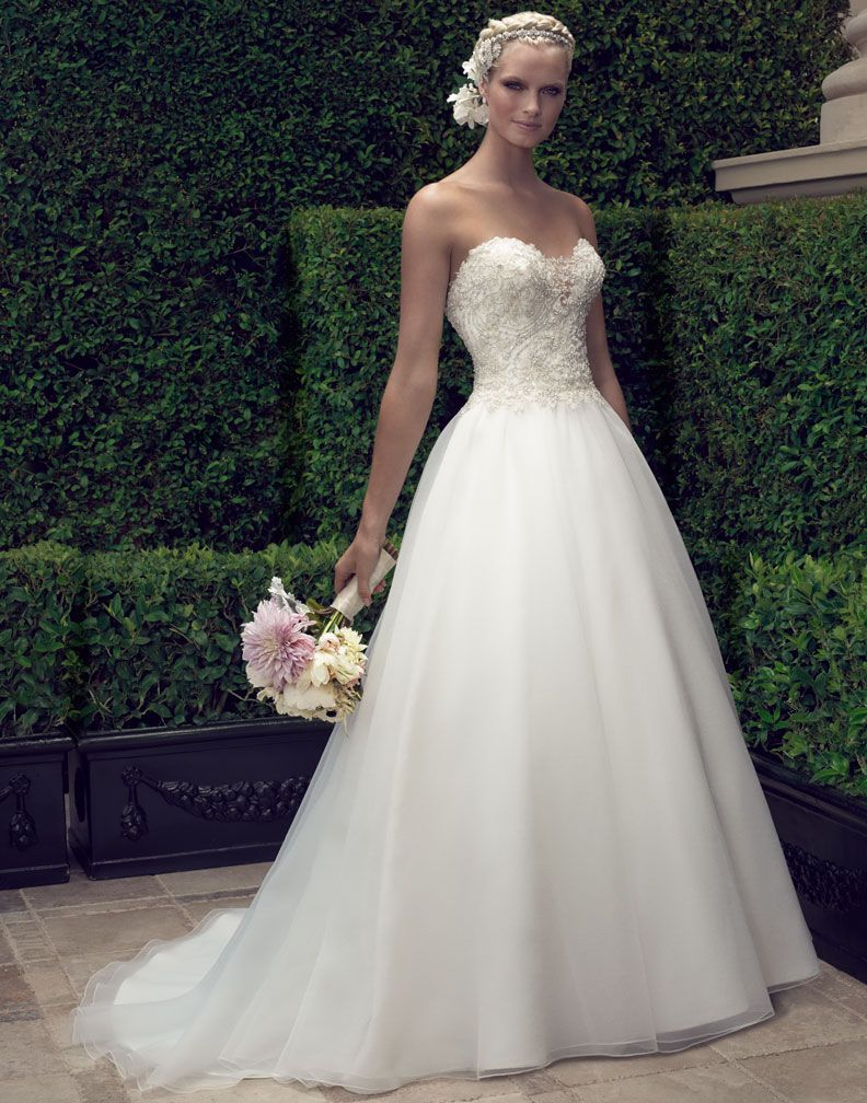 2191 Ball gown features a strapless plunging sweetheart neckline that is decorated with beaded sheer illusion tulle triangle panel at the center front neckline to add the perfect amount of coverage. The heavily beaded and embroidered bodice flows into a gathered Crepe Organza skirt.