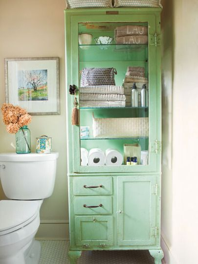 Soft mint green storage shelves with clear door with dark knob and tassle hanging from it.  A series of drawers next to a plain door may be used for smaller items.