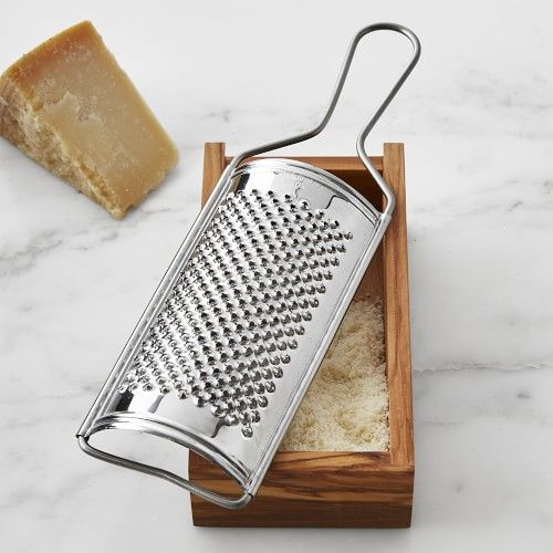 Grate and serve cheese right at the table with this Italian-made design, which pairs gleaming stainless steel with gorgeous olivewood. The grater's fine, sharp perforations are ideal for hard cheeses like Parmigiano-Reggiano or for grating hard chocolate for dessert topping. Simply slide the grater into the box's grooves, grate cheese and then remove the grater and serve. Natural olivewood box with a stainless-steel grater. Grater slides on and off wood box. Grater is dishwasher safe. Made in It