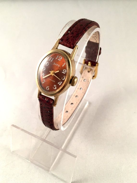 """This is a lovely Vintage mechanical wristwatch called """"Zarja for ladies. This watch was made in Pensa Watch Factory. Mechanical movement, manual winding,17 jewels movement.Lovely deep red dial!  Watch is in fully working order, professionally serviced, premium leather strap included. Made in USSR. Year: 70s  The face is 23 mm long and 19mm wide.  """"Zarja"""" brand was launched in 1965. """"Zarja"""" watches are known for their durability, accuracy and style.  Cosmetic Condition: Good with some obvious…"""