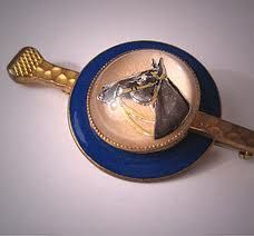 A Fabulous Antique Glass Essex Crystal Enamel Horse Brooch, Equestrian Theme. This wonderful vintage pin is estimated to date circa 1930's Art Deco Era. It has an essex crystal style glass centerpiece with a reverse painted horse at its center. It is surrounded by vibrant blue enamel and is set in gold gilt over brass setting. Overall the pin measures about 2 5/8 inch long by about 1 1/4 inch wide and closes with the original safety clasp. It is in lovely vintage condition.