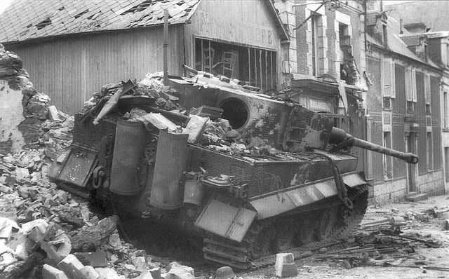 A knocked out Tiger No.121 (late model) of the SS-Panzer Div. shown destroyed in the ruins of Villers-Bocage, rue Pasteur, after the battle of the same name. A shot from a British 6-pounder took her out. A Tiger tank belonged out in the open to be most effective. A heavy tank used in urban areas was at an instant disadvantage...