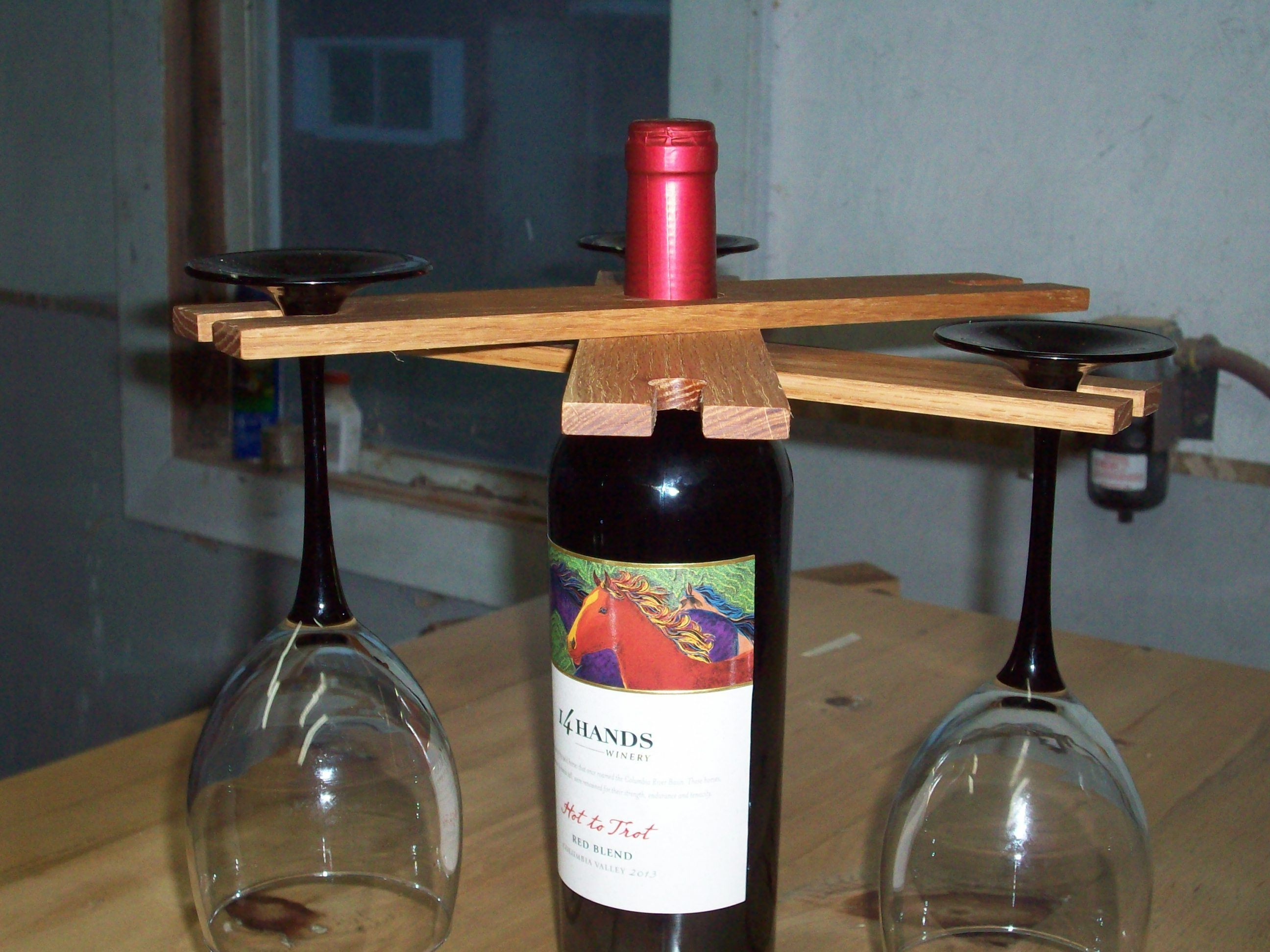 Wine glass holder that fits over neck of wine bottle and can hold 4 or 6 wine glasses.                                                                                                                                                                                 More