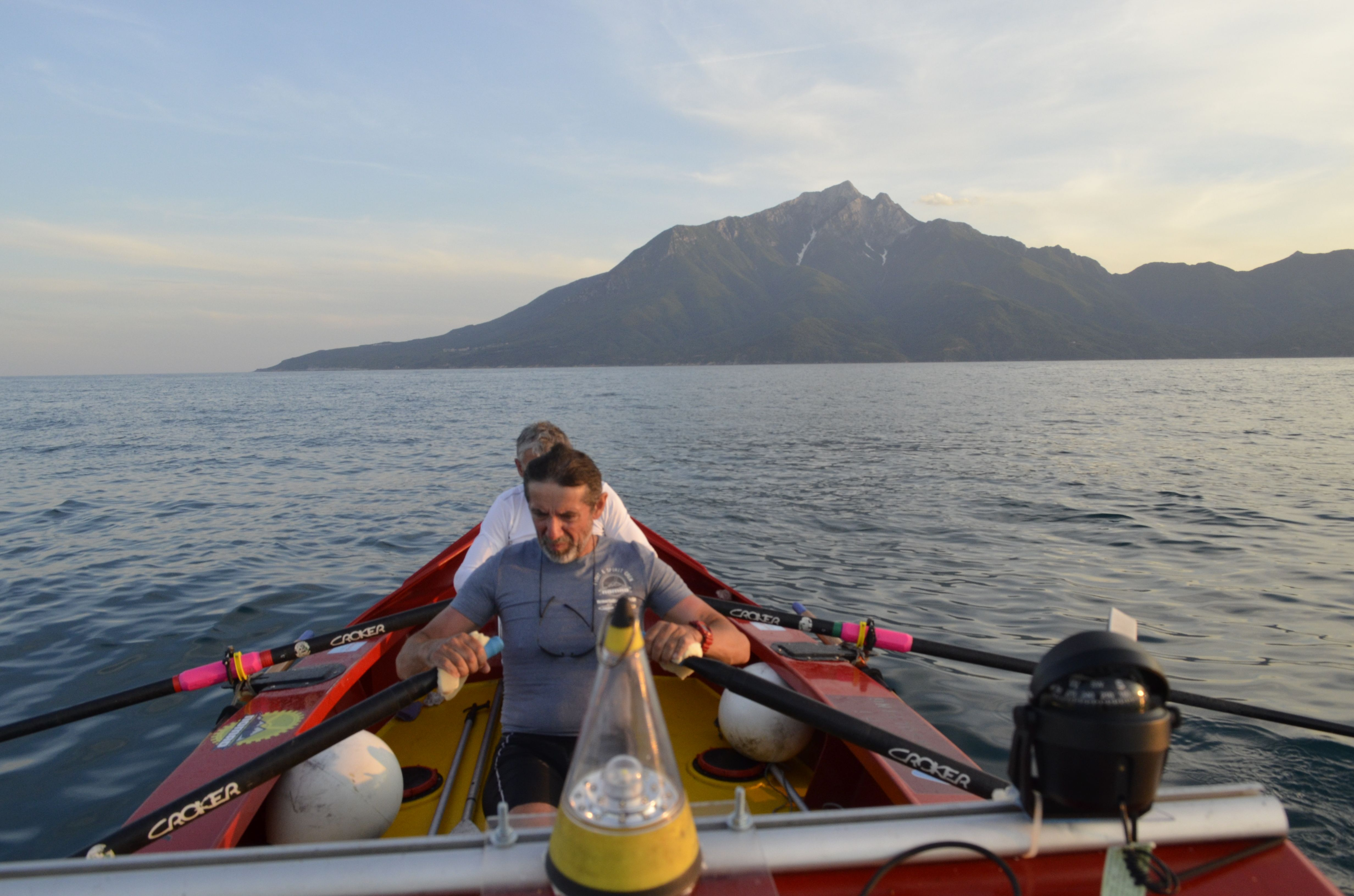 Nomads rowing beneath Holy Mountain Athos, Greece