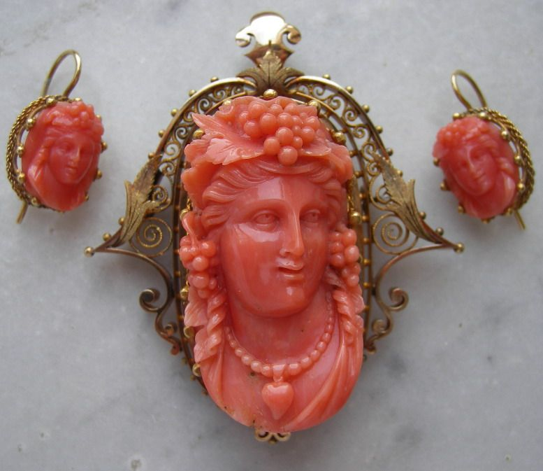 Museum quality cameo set consisting in a brooch and a pair of earrings, both carved with Bacchantes faces (Bacchantes were followers of Bacchus the God of wine, Dionysus is the Greek name). 14k gold and Sardinia Coral, ca. 1860 Italy.