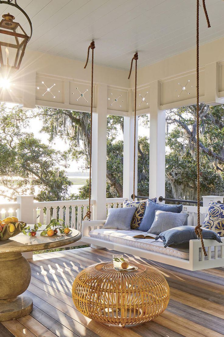 Swing Porch - The 2019 Southern Living Idea House - Beach house decor. Love the bedswing from the Original Charleston swing Company, Zuri decking - looks like hardwood, round table, blue and white accent pillows and copper gas lights - what a water view! Coastal living.    Dream House | Exterior | Interior Design Trends | Dream Home | Rooms | Ideas | Kitchen | Living Room | Bedroom | Bathroom | Garden | Water View | Mansion | Beach Front | Ocean Front Home