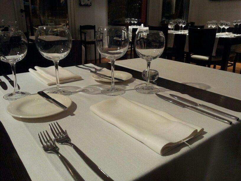 Mesa lista, con sus respectivos cubiertos de entrada, principal, platito de pan, cuchillo para untar, copas de agua y vino.