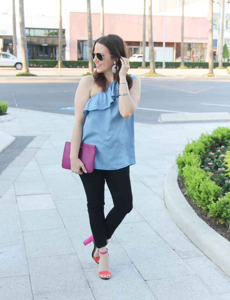 c5811848e3 Houston fashion blogger styles spring outfit idea featuring chambray one  shoulder top with black skinny jeans and block heel sandals.