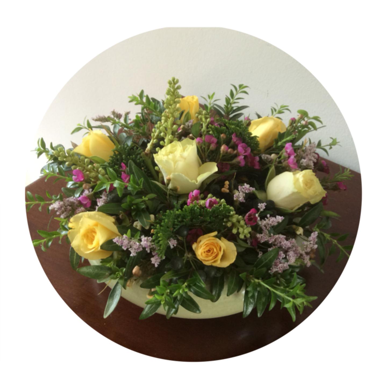 Voorjaarsbloemstukje met roosjes en takjes groen