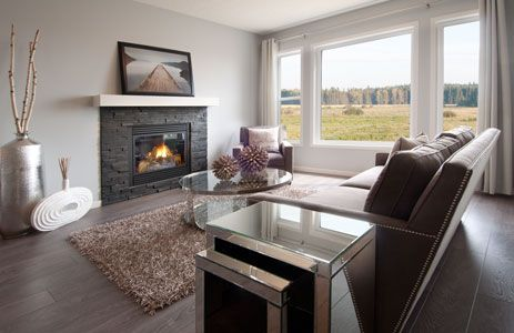 Great Room in the Huntington showhome by Morrison Homes - off white walls with dark hardwood and a stone fireplace