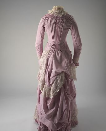 Dating from about 1885, this full length dress is made from fine wool, is pink/musk in colour and is elaborately trimmed with cream lace. The tight-fitting bodice is lined and boned, with a high standing collar trimmed with lace that is identical to that used on the cuffs of the full length sleeves.