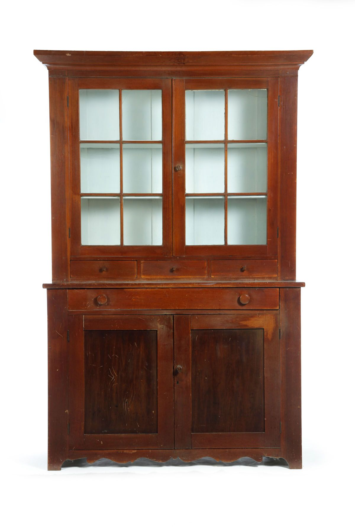 """STEPBACK CUPBOARD. Zoar, Ohio, mid 19th century, walnut and poplar. Two-piece cupboard: the upper section with two six-pane doors and three drawers with their original diamond pulls, the lower section with one drawer and two paneled doors, all on a shaped base. 81.5""""h. 54""""w. 20""""d. Estimate $2,500-5,000 garths.com"""