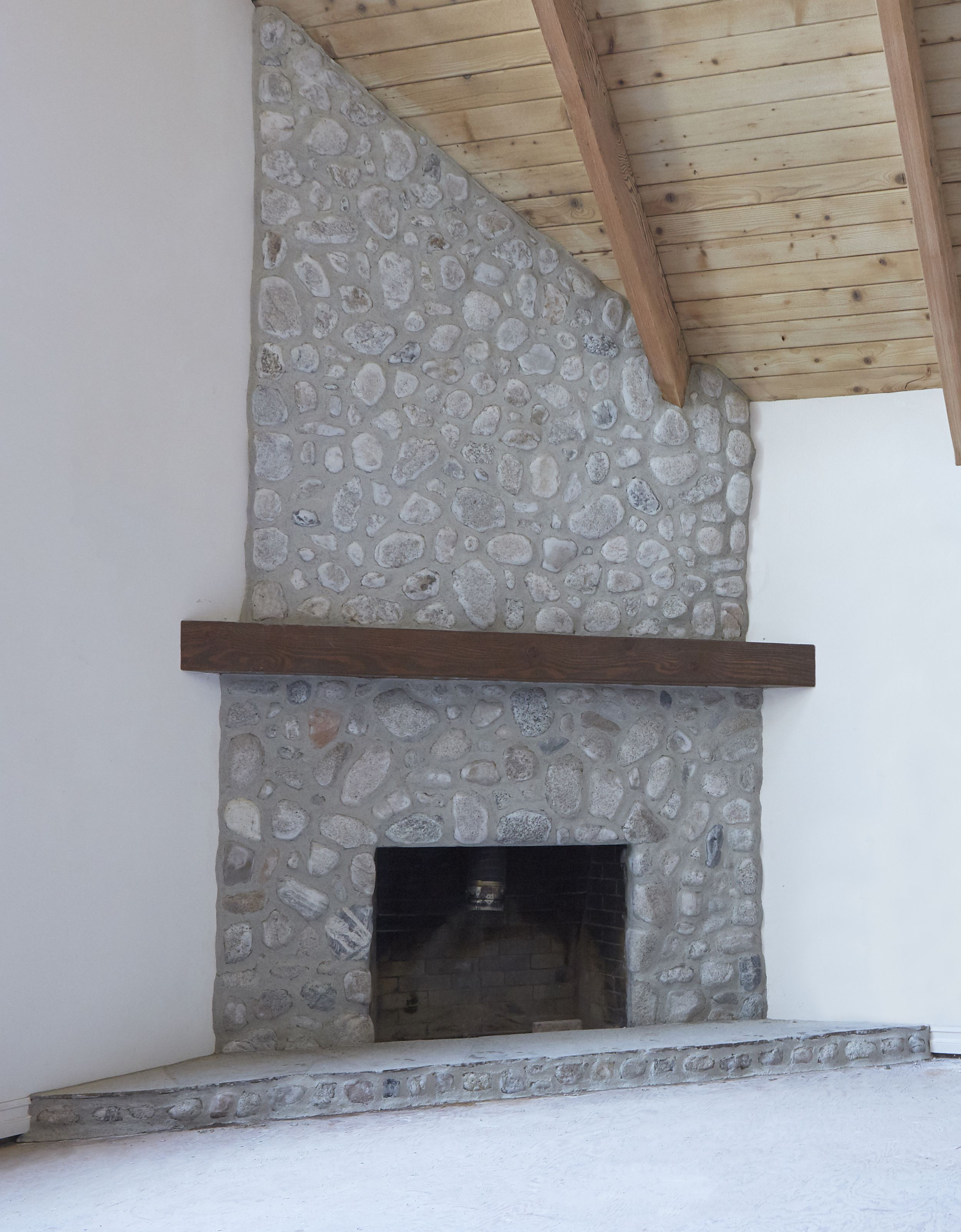 Finished German Schmear River Rock Fireplace