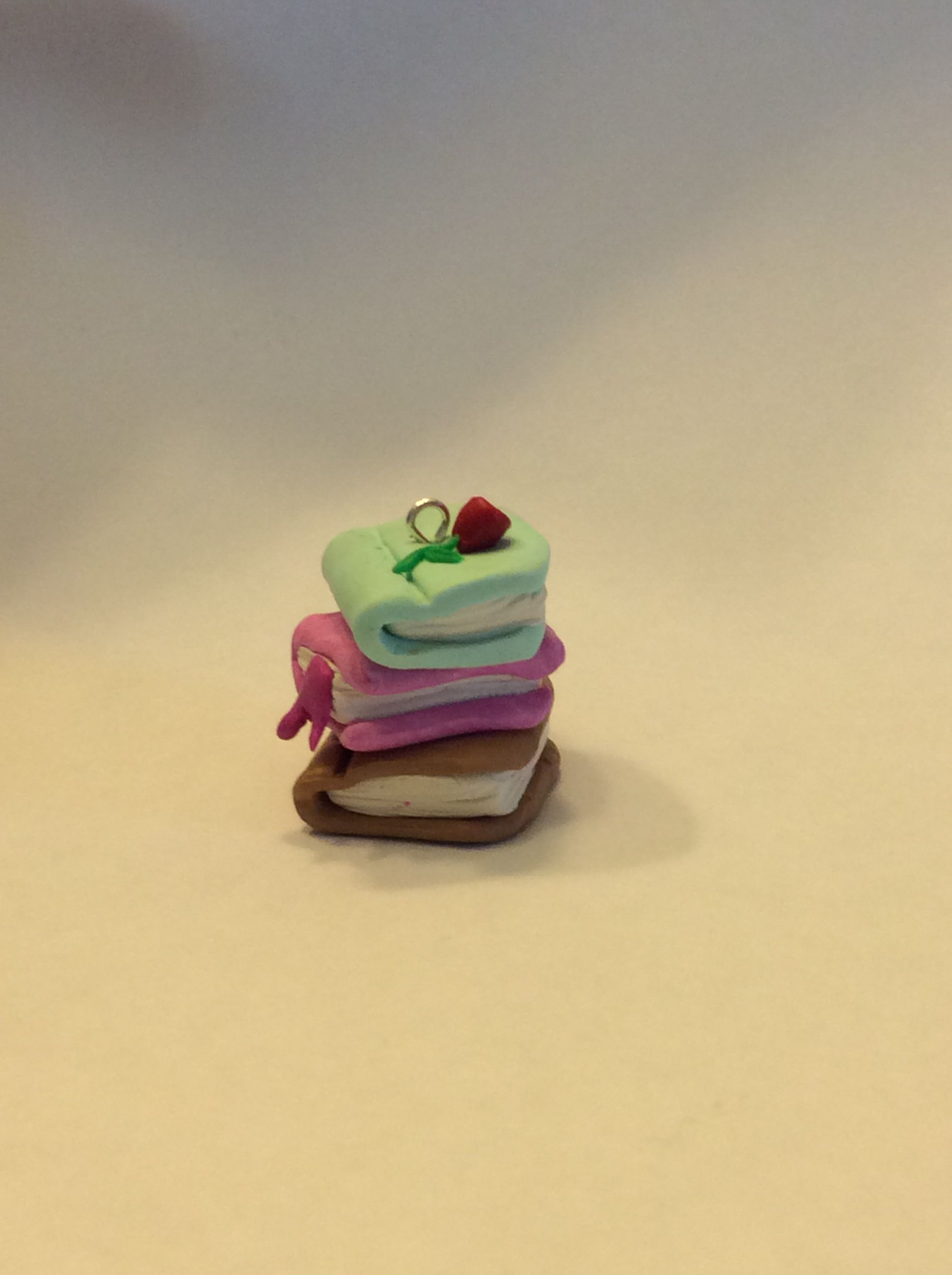 Polymer clay stack of books with a flower on top.